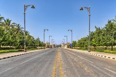 AL Fujayrah, Emiratos Árabes Unidos A vista de uma rua pavimentada vazia, com os revérbero dourados bonitos marcou as passagens p imagens de stock royalty free