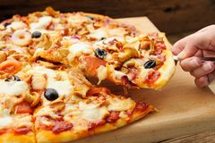 Al funghi pizza cut in sectors with one piece taken in hand Royalty Free Stock Photography