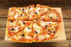 Al funghi pizza with olives cut in sectors on wooden board Stock Photos