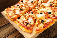 Al funghi pizza with olives cut in sectors on wooden board Stock Image