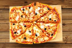 Al funghi pizza with olives cut in sectors on wooden board Stock Photo