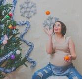 Al lado de árbol la muchacha embarazada lanza naranjas en el Año Nuevo Fotos de archivo libres de regalías