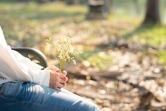 Al lado de la mujer joven de la visión que sostiene la flor blanca del ramo que se sienta encendido Foto de archivo libre de regalías