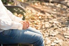 Al lado de la mujer joven de la visión que sostiene la flor blanca del ramo que se sienta encendido Foto de archivo