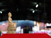 Al lado de la resina beige del color de la estatua de Buda Un Buda tallado fi Imágenes de archivo libres de regalías