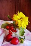 Al lado del vidrio con una flor amarilla y bayas rojas son dos s Foto de archivo
