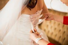Al legame della sposa un vestito Immagini Stock Libere da Diritti