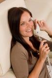 Al mujer del teléfono llamar sonriente casera Imágenes de archivo libres de regalías