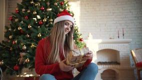 Al Natale, una bella ragazza ha trovato un regalo sotto l'albero Concetto: magia, Natale, regalo, feste archivi video