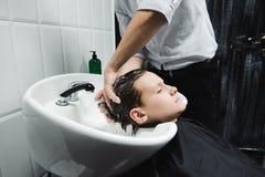 Al peluquero en la barbería lava a un muchacho fotos de archivo