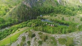 Al piede delle montagne vicino ad un piccolo fiume è un piccolo stabilimento video d archivio