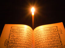 Al-Quran. And candle light stock photos