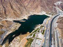 Al Rafisah Dam in Khor Fakkan in the United Arab Emirates. Aerial view lake uae water sharjah reservoir desert mountain sandstone highway road rock above drone stock photography