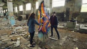 Al rallentatore degli artisti dei graffiti stanno usando la pittura dell'aerosol per decorare il fabbricato industriale abbandona video d archivio
