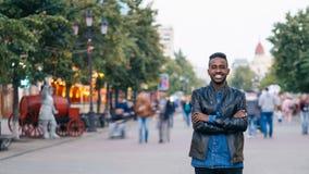 Al rallentatore dell'uomo afroamericano sorridente stare da solo nel centro urbano con le mani ha attraversato godere della vita  video d archivio