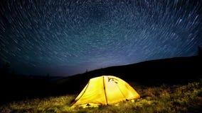 al rallentatore Star i cerchi sopra le montagne di notte e una tenda di campeggio d'ardore archivi video