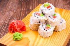 Al revés rollo de sushi con los salmones y el aguacate Imagen de archivo libre de regalías