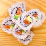 Al revés rollo de sushi con los salmones y el aguacate Fotografía de archivo