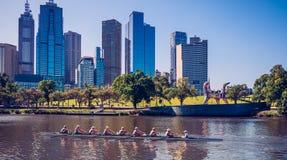 Al roeiend teamlid in de boot duwt hun beste op de rivier stock foto's