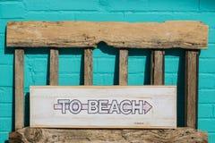 Al segno di legno bianco della spiaggia Immagini Stock