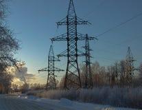 Al tramonto nell'inverno, supporto ad alta tensione fotografia stock