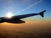 Ala de aviones de jet en la puesta del sol Foto de archivo libre de regalías