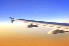 Ala de aviones en luz de la salida del sol Foto de archivo libre de regalías