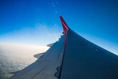 Ala de la línea roja vuelo del aeroplano de la compañía sobre la tierra Imagenes de archivo