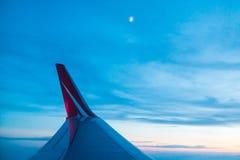 Ala de la línea roja vuelo del aeroplano de la compañía sobre la tierra Imagen de archivo libre de regalías
