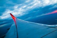 Ala de la línea roja vuelo del aeroplano de la compañía sobre la tierra Imagen de archivo