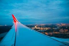 Ala de la línea roja vuelo del aeroplano de la compañía sobre la tierra Fotografía de archivo libre de regalías