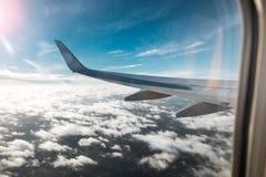 Ala de un aeroplano sobre las nubes, fondo de un cielo azul La foto fue tomada de la ventana del avión Fotos de archivo libres de regalías