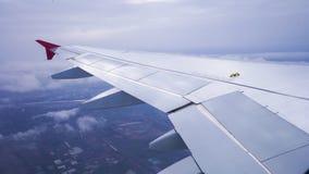 Ala de un vuelo del aeroplano sobre el cielo con las nubes