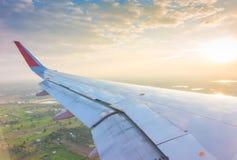 Ala de un vuelo del aeroplano sobre las nubes en la puesta del sol Imágenes de archivo libres de regalías