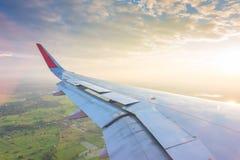Ala de un vuelo del aeroplano sobre las nubes en la puesta del sol Imagenes de archivo