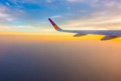 Ala de un vuelo del aeroplano sobre las nubes en la puesta del sol Fotografía de archivo
