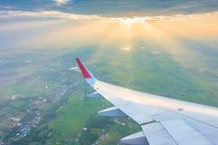 Ala de un vuelo del aeroplano sobre las nubes en la puesta del sol Imagen de archivo