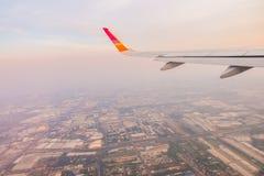 Ala de un vuelo del aeroplano sobre las nubes en la puesta del sol Foto de archivo