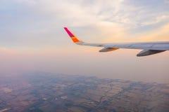 Ala de un vuelo del aeroplano sobre las nubes en la puesta del sol Fotografía de archivo libre de regalías