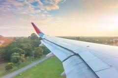 Ala de un vuelo del aeroplano sobre las nubes en la puesta del sol Fotos de archivo libres de regalías