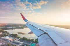 Ala de un vuelo del aeroplano sobre las nubes en la puesta del sol Imagen de archivo libre de regalías