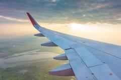 Ala de un vuelo del aeroplano sobre las nubes en la puesta del sol Fotos de archivo