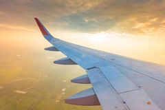 Ala de un vuelo del aeroplano sobre las nubes en la puesta del sol (Filtro Fotos de archivo libres de regalías