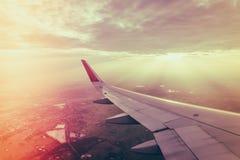 Ala de un vuelo del aeroplano sobre las nubes en la puesta del sol (Filtro Imágenes de archivo libres de regalías