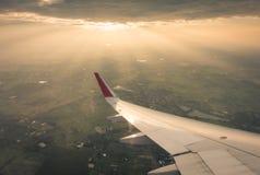 Ala de un vuelo del aeroplano sobre las nubes en la puesta del sol (Filtro Imagen de archivo libre de regalías