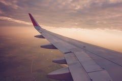 Ala de un vuelo del aeroplano sobre las nubes en la puesta del sol (Filtro Fotografía de archivo libre de regalías