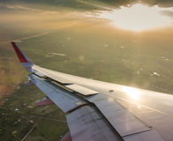 Ala de un vuelo del aeroplano sobre las nubes en la puesta del sol (Filtro Foto de archivo