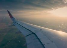 Ala de un vuelo del aeroplano sobre las nubes en la puesta del sol (Filtro Foto de archivo libre de regalías