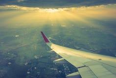 Ala de un vuelo del aeroplano sobre las nubes en la puesta del sol (Filtro Imagenes de archivo