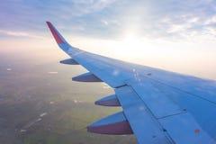 Ala de un vuelo del aeroplano sobre las nubes en la puesta del sol (Filtro Imagen de archivo